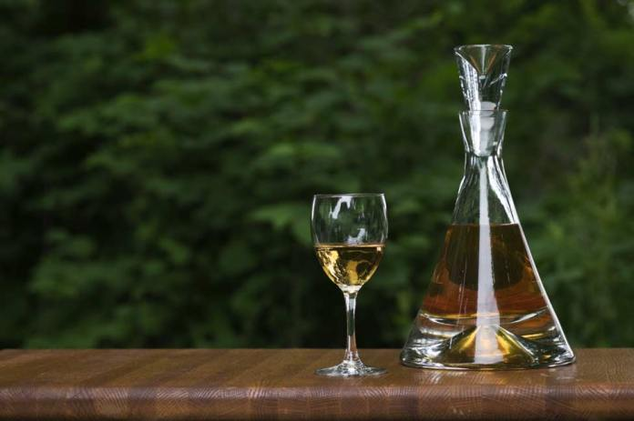 A snifter of Brandy with a decanter sitting on an oak table top.